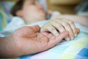 Frau Krankenhausbett Hand halten