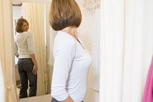 Frau vor Spiegel Figur betrachten