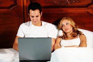 Paar Bett Mann mit Laptop