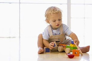 Kleinkind sitzt und spielt Panther Monkeybusiness Images