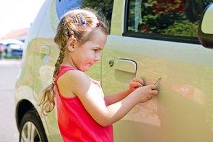 Mädchen zerkratzt Auto mit Schlüssel
