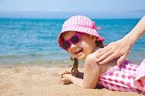 Mädchen am Strand mit Sonnenhut