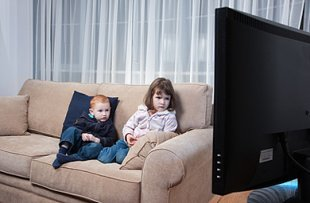 Kinder auf dem Sofa vor dem Fernseher