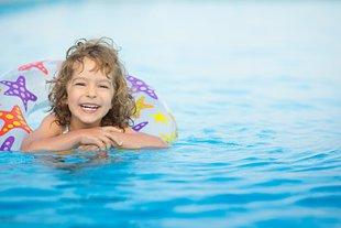 Kind mit Schwimmreifen im Wasser