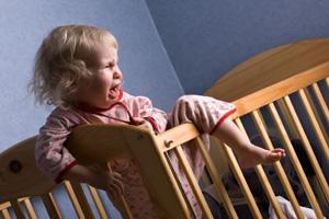 Gitterbett Kleinkind steht weint