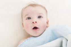 Ein staunender Junge in einen blauen Strampler