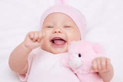 Ein lachendes Mädchen in rosa Strampler