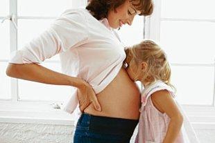 Geschwisterkind kuesst Bauch