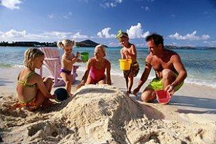 Familie am Strand mit Sand spielend