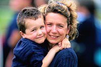 Mutter traegt umarmt Junge