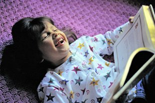 Maedchen lesend lachend