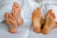 Fuesse Paar nebeneinander Bett