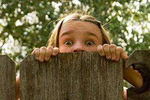 Maedchen frech hinter Zaun