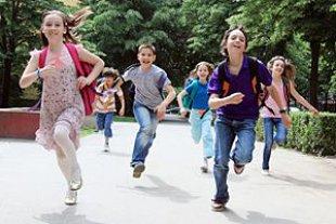 Kinder mit Schulranzen laufen