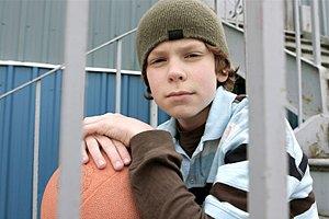 Junge allein vor Haus mit Ball