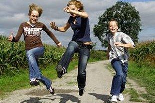 Kinder springen Feldweg