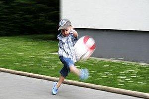 Junge Ballspiel wild