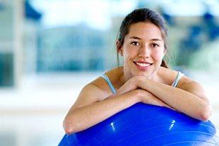 Frau lehnt auf Gymnastikball