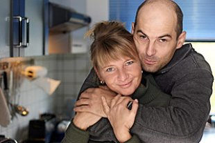 Paar umarmt sich Kueche