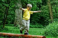 Junge balanciert Baumstamm