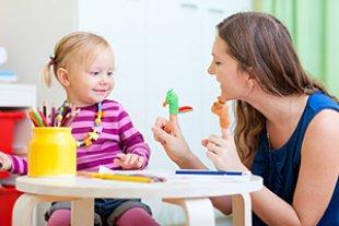 Babysitterin Mädchen spielen Tisch