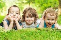 Drei Kleinkinder im Gras
