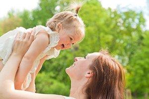 Mutter hält kleines Mädchen lachend hoch