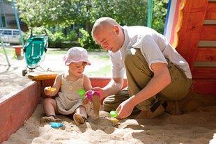 Vater spielt mit Tochter im Sandkasten