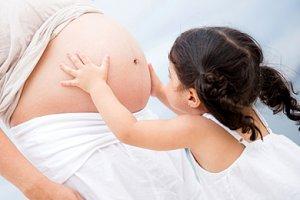 Mädchen streichelt Babybauch