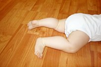 Baby in kurzem Body krabbelt aus dem Bild