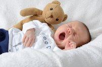 Baby gähnt Kuscheltier