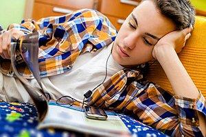 Teenager liest und hört Musik
