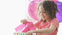 Mädchen packt Geschenke aus