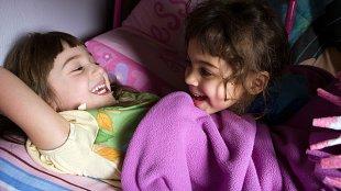Mädchen Bett lachen