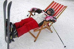 Kind mit Skiern im Liegestuhl