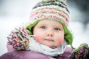 Baby mit Mütze im Schnee