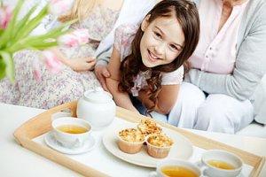 Mutter und Tochter am Tisch mit Kuchen und Tee