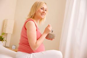 Schwangere Essen auf Bett